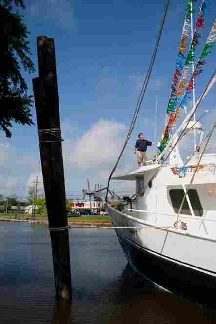 "Before the Blessing of the Fleet, shrimp trawlers are painstakingly decorated with streamers and signs. Here, David Chauvin pauses to inspect the decorations on his boat, the ""Mariah Jade. """