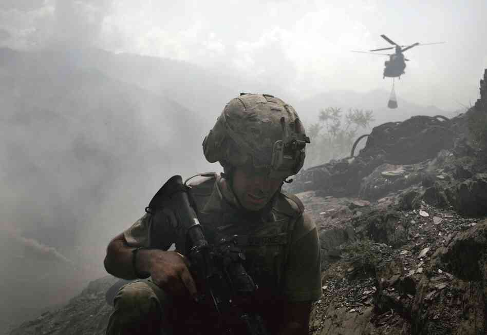 A soldier takes cover from the dust being generated by an incoming Chinook helicopter delivering supplies to the Restrepo base. The image is from Hetherington's book Infidel.