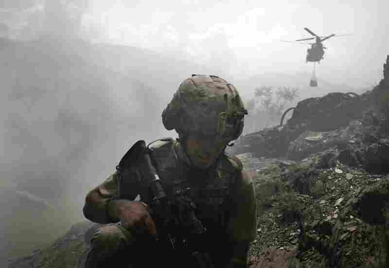 A soldier takes cover from the dust being generated by an incoming Chinook helicopter delivering