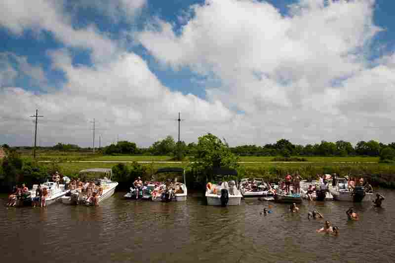 Families and friends tie their boats along the bayou to watch the annual ceremony and procession.