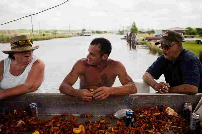 P.J. Domaingue (center) eats boiled crawfish with friends and family aboard his boat, the Maycie Brooke. Domaingue, whose boat was voted best-decorated last year, had the honor of hosting the priests at the front of the parade in this year's ceremony.