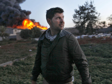 Getty Images photographer Chris Hondros stands in front of a burning building while on assignment on April 18, in Misrata, Libya. Hondros was killed in Misrata on April 20.