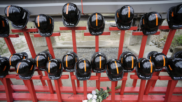 Mine helmets and painted crosses sat at the entrance to Massey Energy's Upper Big Branch coal mine on April 5, as a memorial to the 29 miners killed there one year earlier. (AP)