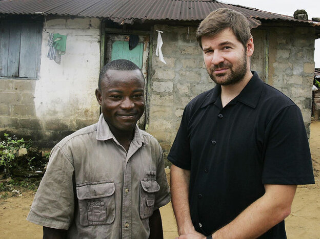 Photojournalist Chris Hondros poses with a a former Liberian government soldier in Monrovia, Liberia, in 2005.