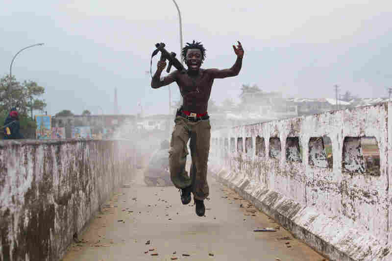 Joseph Duo, a Liberian militia commander loyal to the government, exults after firing a rocket-propelled grenade at rebel forces at a key strategic bridge in Monrovia, Liberia, on July 20, 2003.