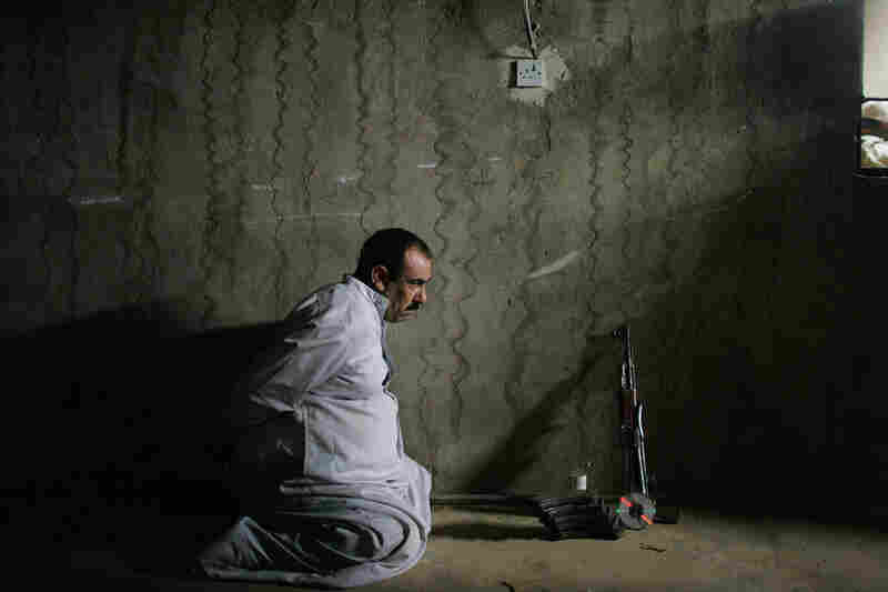A detained man waits to be photographed by Marines for processing with the weapons allegedly found with him, June 24, 2005, near Fallujah, Iraq.