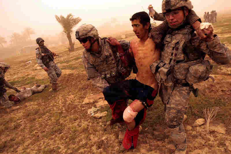 Medic Sgt. Matthew Kunkle (left) and Pvt. Aaron Livas carry a wounded Iraqi man in Baghdad on May 16, 2008. The man had been shot in the leg by U.S. troops after trying to flee from them. He was immediately treated by the U.S. medic traveling with the platoon and transported to the nearest base for medical care.