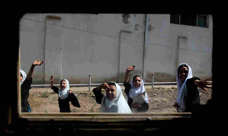 Afghan schoolgirls seen through the window of a Humvee wave to a passing American convoy in downtown Herat, Afghanistan, on June 26, 2010.