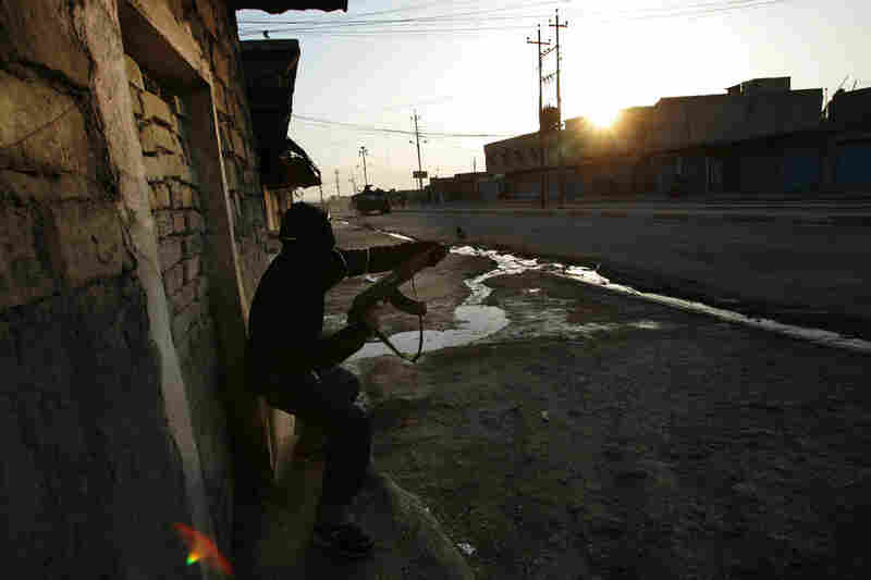 An Iraqi police officer fires at attacking insurgents during a Jan. 16, 2005, firefight in Tal Afar, Iraq. A routine patrol in the insurgent stronghold turned into an hourlong running gun battle with a combined U.S. and Iraqi police force battling insurgents across alleys and down boulevards.