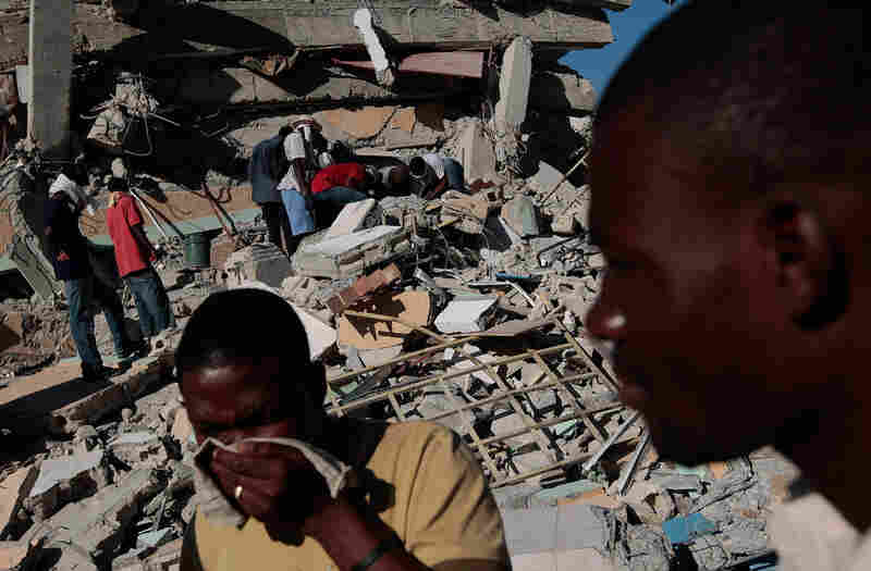 Haitians pass in front of the collapsed multistory St. Gerard School in Port-au-Prince on Jan.15, 2010.
