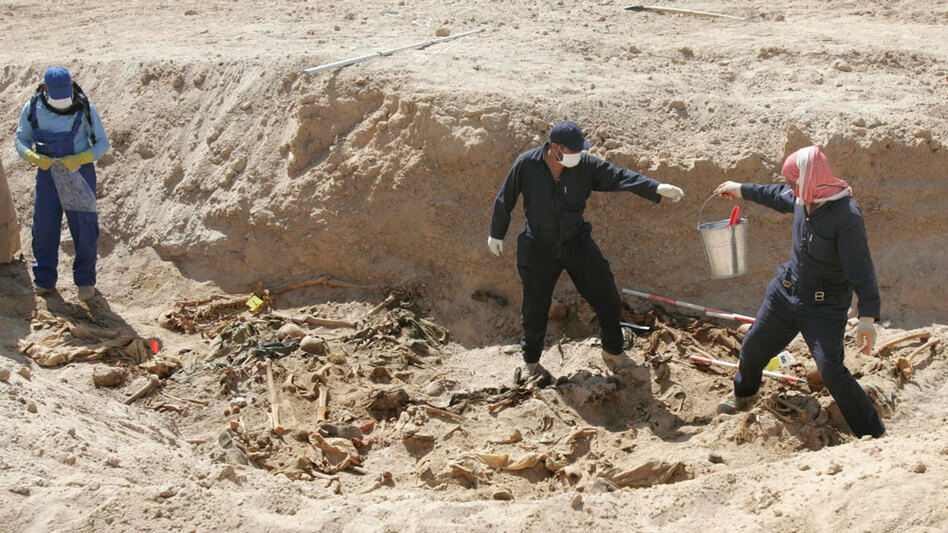 Workers excavate remains from a mass grave in the desert of western Anbar province in Iraq on April 14. The mass grave holds the remains of more than 800 people, believed to have been killed during the rule of ousted leader Saddam Hussein.