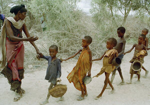 In 1992, Marinovich traveled to Somalia to document the war and famine. In this photo, a woman leads children — who had been waiting all day to be fed — to a food kitchen.