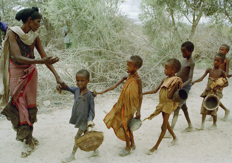 In 1992, Marinovich traveled to Somalia to document the war and famine. In this photo, a woman leads children — who had been waiting all day to be fed — to a food kitchen.  (AP)