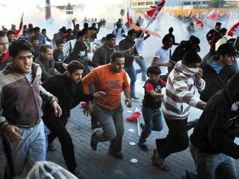 Bahraini  protesters run for cover from tear gas fired by police in the village of Sanabis  near Manama during a demonstration on Feb. 14.