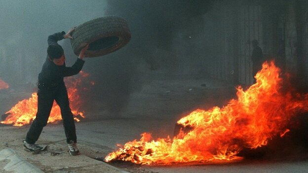 In the late 1990s, both Marinovich and Silva traveled to the Middle East to photograph the ongoing clashes in the region. Silva captured this image of a young Palestinian boy throwing a tire in the West Bank town of A-Ram in March 1997. (AP)