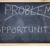 """The word """"problem"""" is crossed out on a blackboard and replaced with the word opportunity."""