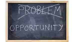 "The word ""problem"" is crossed out on a blackboard and replaced with the word opportunity."