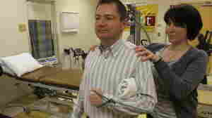Orthopedist Popi Gianakouras helps 45-year-old Bob Rothaker with physical therapy to treat his sore shoulder.