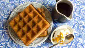 Belgian-style waffles on a plate, with a pitcher of maple syrup and a bowl of orange whipped cream on the side