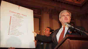 """Then-House Speaker Newt Gingrich holds up a copy of the Republican Party's """"Contract with America"""" during a rally to celebrate the first 50 days of the Republican majority in Congress in 1995."""