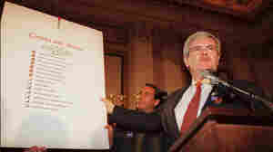 "Then-House Speaker Newt Gingrich holds up a copy of the Republican Party's ""Contract with America"" during a rally to celebrate the first 50 days of the Republican majority in Congress in 1995."
