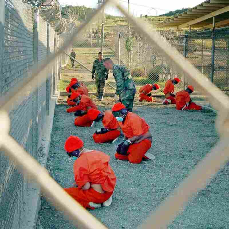 Suspected Taliban and al-Qaida detainees sit in a holding area at Camp X-Ray at Guantanamo Bay, Cuba, during in-processing to the temporary detention facility.