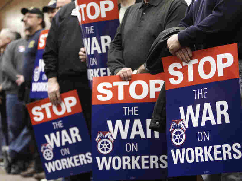 Public employees hold protest signs at an April 4 union rally in Cleveland.