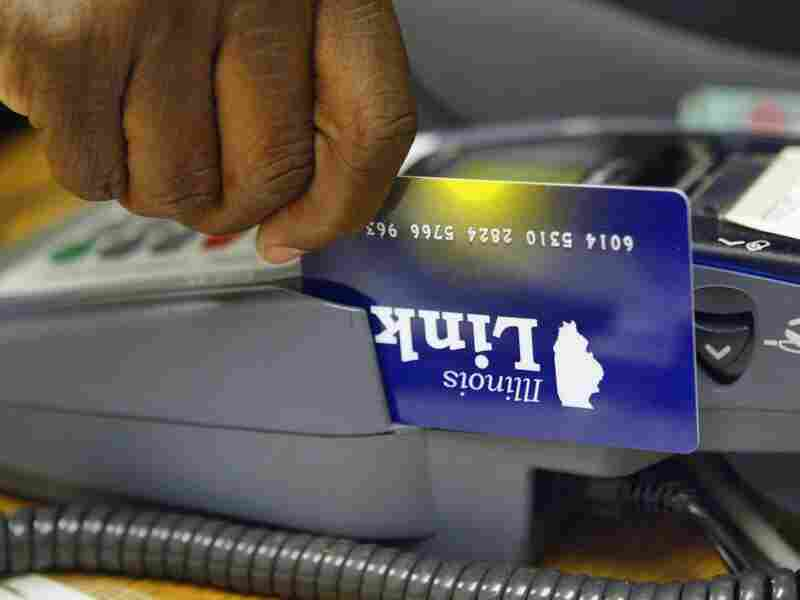 A clerk at the Illinois Department of Human Services demonstrates the activation of an Illinois Link card, an electronic debit-like card used in place of the traditional food stamp.