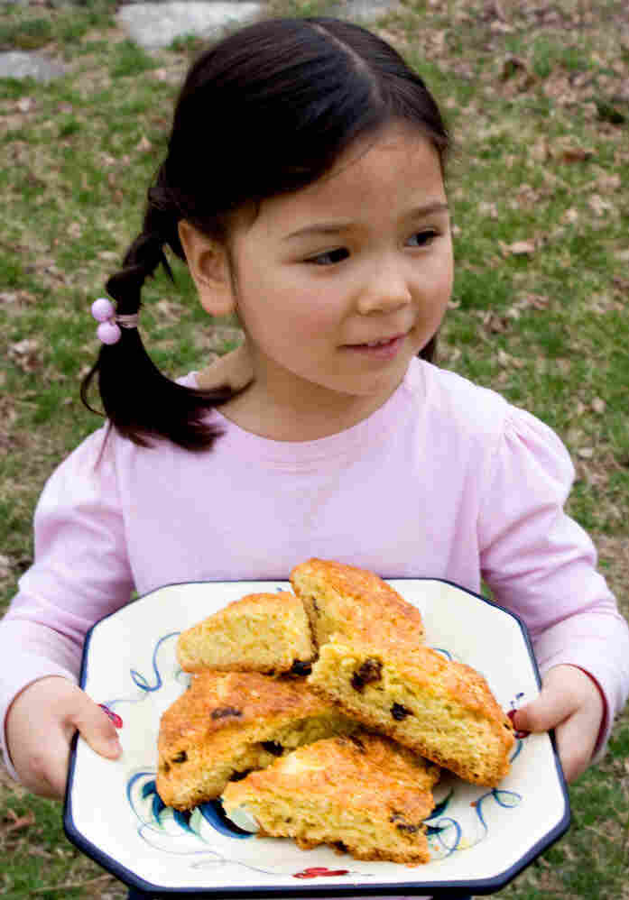 Zoe carries a platter of moist, tangy Cranberry-Orange Scones.