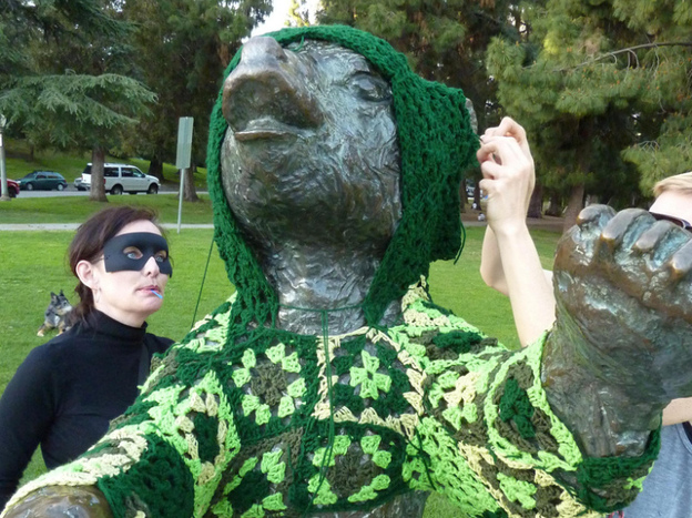"Captain Hook (left) and her accomplice, Vanessa XKiller, vandalize a bear statue in L.A.'s Griffith Park in the most cozy way possible: with a hand-crocheted hoodie. Stepping back to assess their handiwork, Vanessa concludes, it's ""gangster cute."""