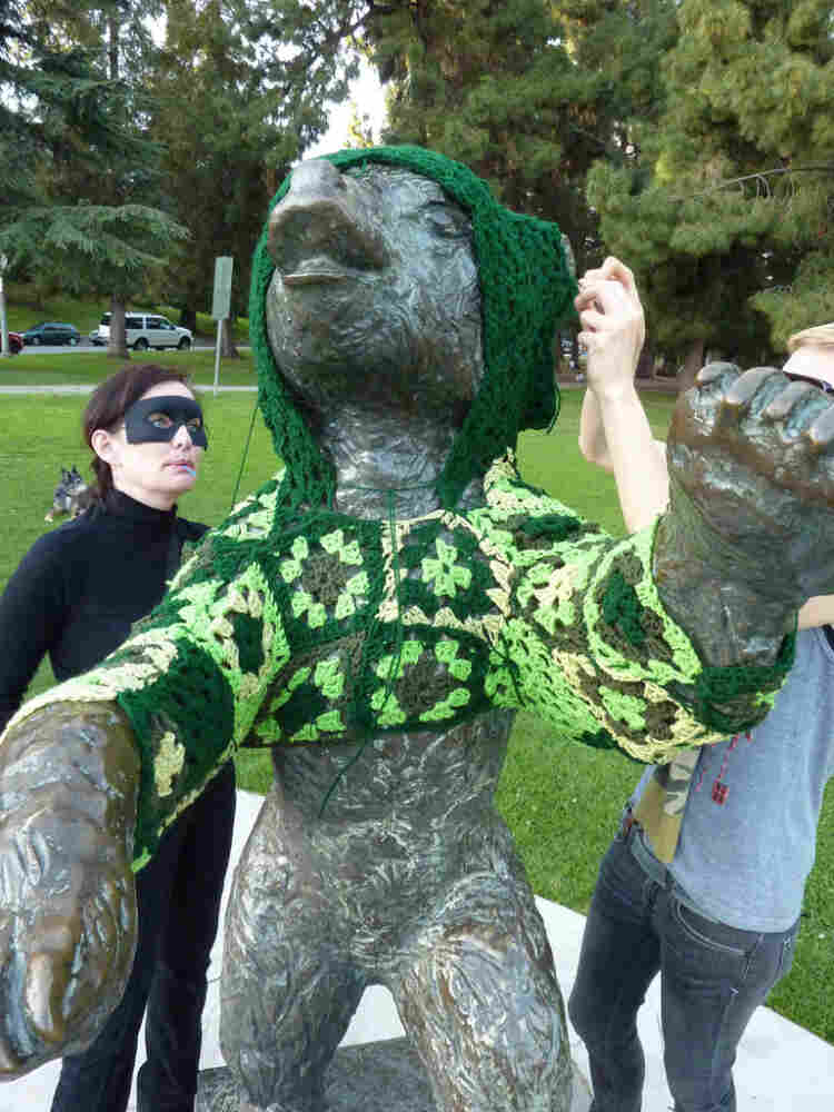 """Captain Hook (left) and her accomplice, Vanessa XKiller, vandalize a bear statue in L.A.'s Griffith Park in the most cozy way possible: with a hand-crocheted hoodie. Stepping back to assess their handiwork, Vanessa concludes, it's """"gangster cute."""""""