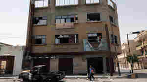 A man walks past a shattered building in Ajdabiya.