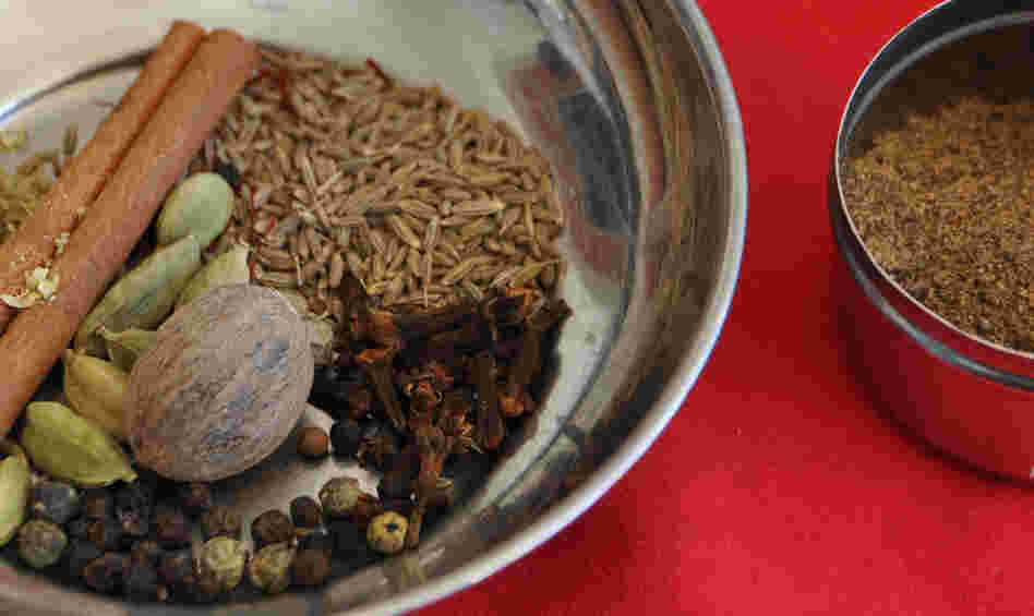 A bowl containing components of garam masala spice, and a bowl of the ground spices