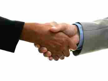 Two people shake hands. People of different backgrounds often grow up speaking their own versions of English slang.
