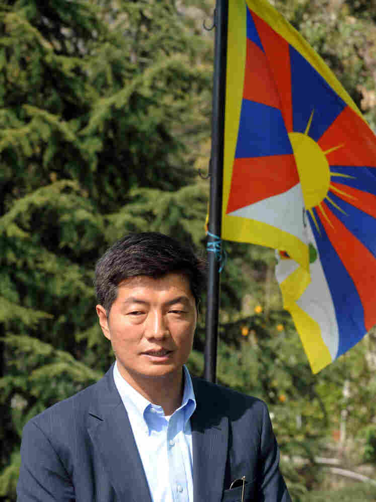 The Prime Minister-elect of Tibet's government-in-exile, Lobsang Sangay, standing by the Tibetan flag.