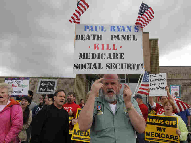 Protesters in Kenosha, Wis., stand outside one of Ryan's listening sessions.