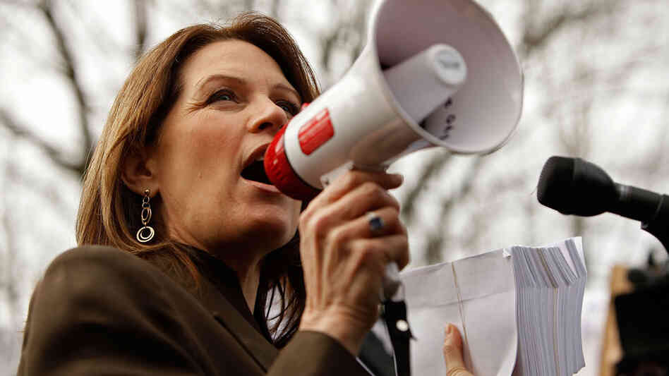 "Rep. Michele Bachmann (R-MN), holding a stack of petitions, addresses a ""Code Red"" rally on Capitol Hill in March 2010, sponsored by The American Grassroots Coalition and the Tea Party Express. The rally was in opposition to the health care overhaul bill."