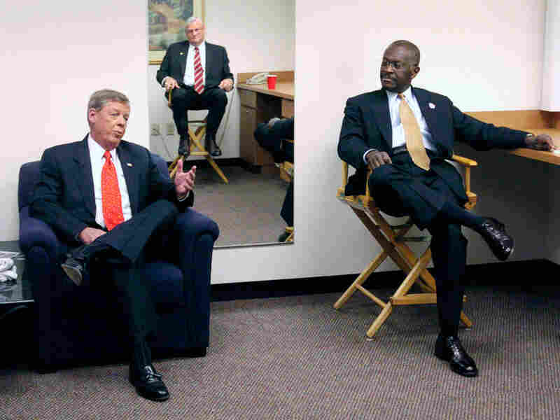 Cain, Johnny Isakson (left) and Mac Collins (reflected in the mirror on the wall) wait before the start of a debate in Atlanta in 2004. The three were running for the U.S. Senate seat then held by Zell Miller.