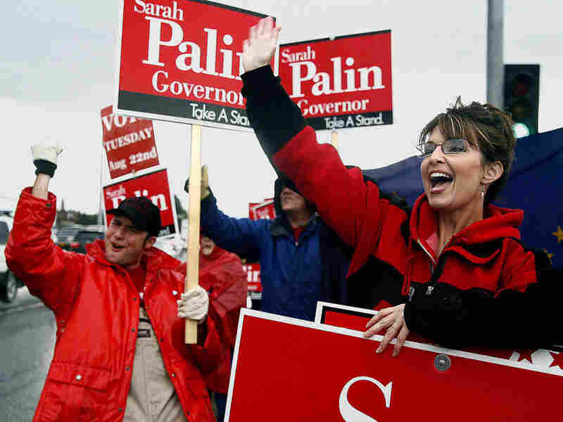 Sarah Palin stands in the rain in Anchorage, Alaska, with Robert Robl (left) and other supporters as she campaigns for the Republican gubernatorial nomination in the primary election Aug. 22, 2006.