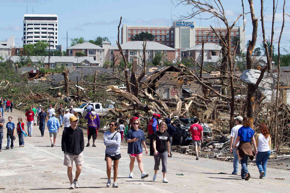 Residents wander the streets near downtown Tuscaloosa surveying the damage on Thursday. President Obama is headed to the area today. The tornado that touched down in Tuscaloosa was estimated to be one mile wide.