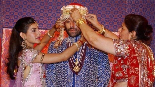 An Indian groom gets his turban arranged by his mother and  sister in law  while his bride greets  guests before their wedding ceremony in New Delhi.