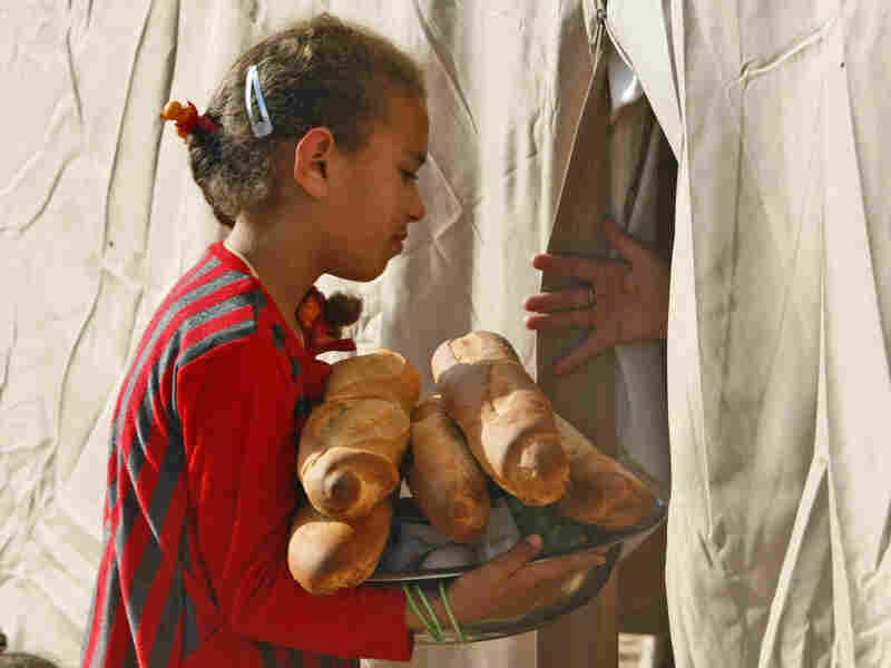 A Libyan girl brings bread into her tent at the U.A.E. Red Crescent refugee camp at the Tunisian village of Dhuheiba on April 22.