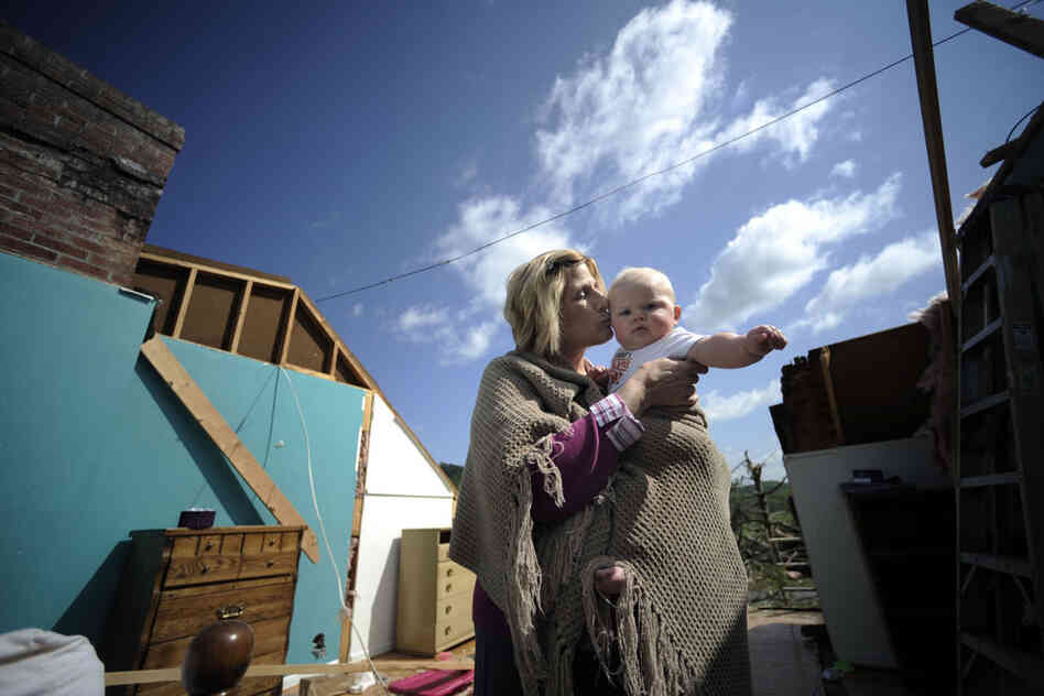 Gail Gilland, 58, holds her 6-month-old grandson, Major Sealey, amid the wreckage of her home in Bethel, Va., Friday. Gilland survived a tornado early Thursday morning by hiding under her bed and riding out the storm while her husband, James, was trapped in the hallway.