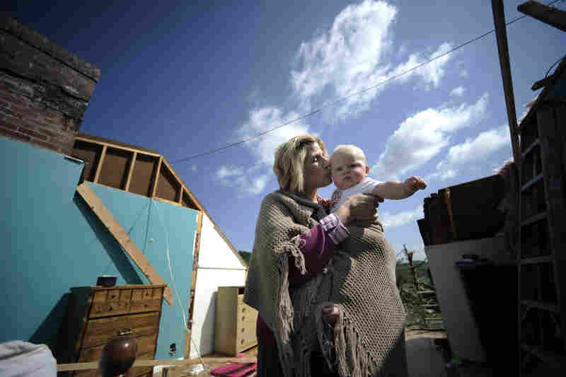 Gail Gilland, 58, holds her 6-month-old grandson, Major Sealey, amid the wreckage of her home in Bethel, Va., Friday. Gilland survived a tornado ea