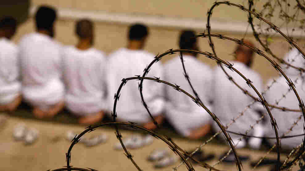 """A group of detainees kneels during an early-morning Islamic prayer in their camp at the U.S. military prison for """"enemy combatants"""" in 2009 in Guantanamo Bay, Cuba."""