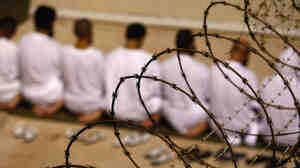 "A group of detainees kneels during an early-morning Islamic prayer in their camp at the U.S. military prison for ""enemy combatants"" in 2009 in Guantanamo Bay, Cuba."