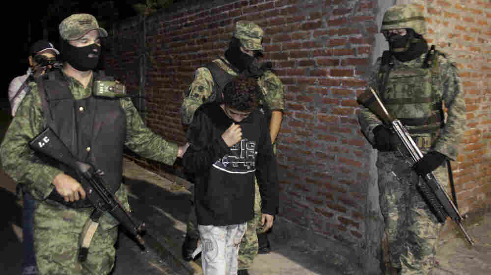 """Soldiers escort 14-year-old Edgar Jimenez Lugo, also known as """"El  Ponchis,"""" after his arrest in the city of Cuernavaca, Mexico, last  December. Jimenez is suspected of working as a killer for a drug cartel  and confessed to participating in four beheadings."""
