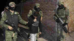 "Soldiers escort 14-year-old Edgar Jimenez Lugo, also known as ""El  Ponchis,"" after his arrest in the city of Cuernavaca, Mexico, last  December. Jimenez is suspected of working as a killer for a drug cartel  and confessed to participating in four beheadings."