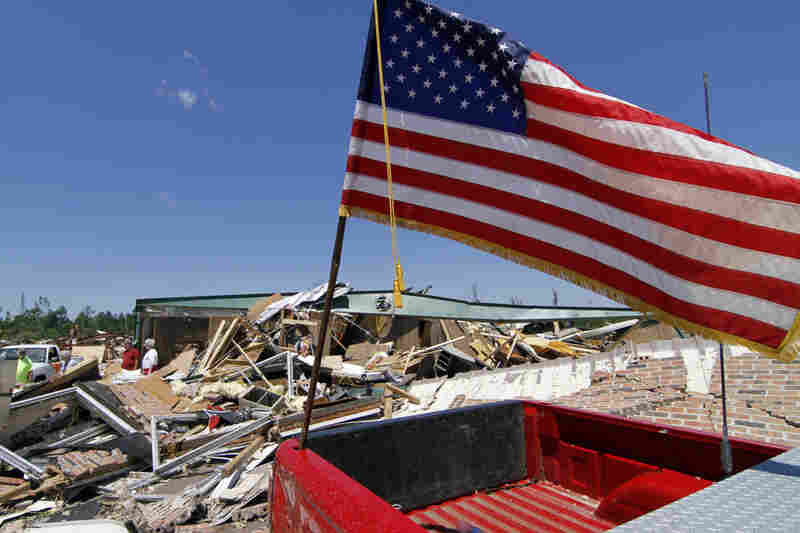An American flag flies atop a destroyed pickup truck outside the remains of the town hall in Smithville, Miss.
