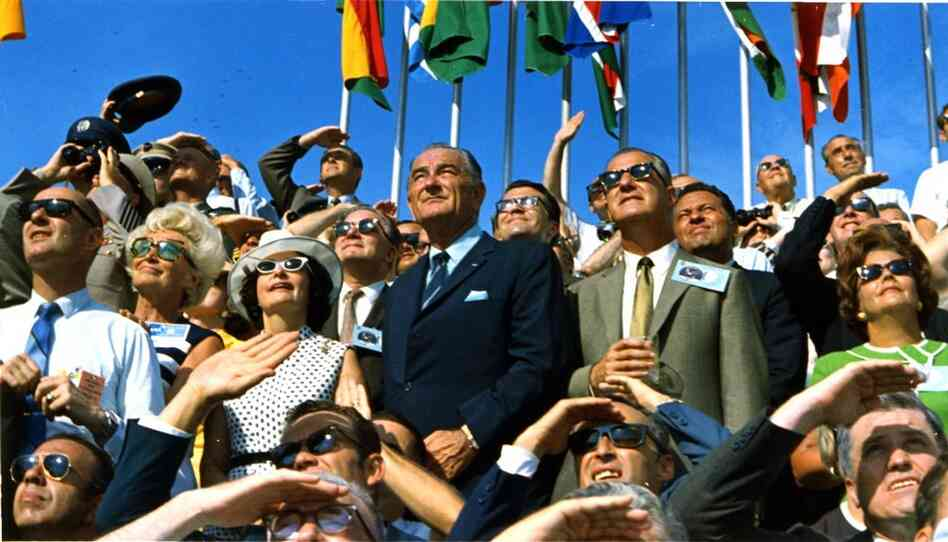 Former President Lyndon B. Johnson (center left) and Vice President Spiro Agnew watch Apollo 11 lift off toward the moon from Kennedy Spac